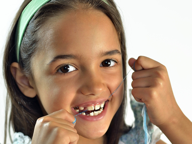 little-girl-flossing-teeth-dr-dennis-dunne-dds
