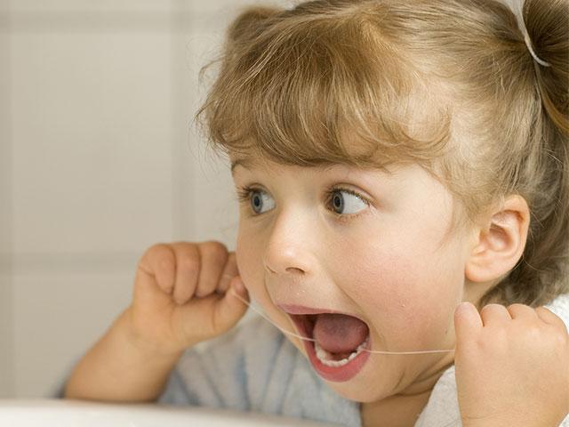cute little girl flossing
